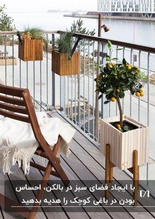 بالکن کوچک خانه ای با گلدان های چوبی مربعی شکل روی نرده