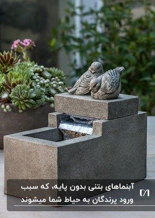 آبنمایی بتنی کف حیاط با مجسمه دو کبوتر بتنی بالای آبنما