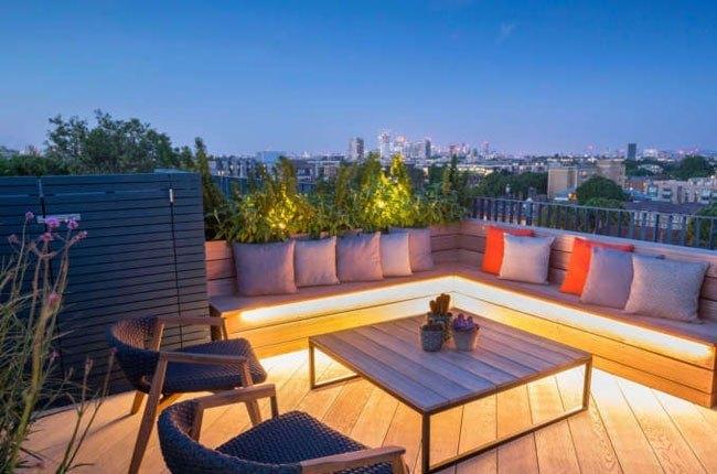 تصویر بام سبزی با نیمکت ال چوبی با کوسن های رنگی و نورپردازی لبه های نیمکت