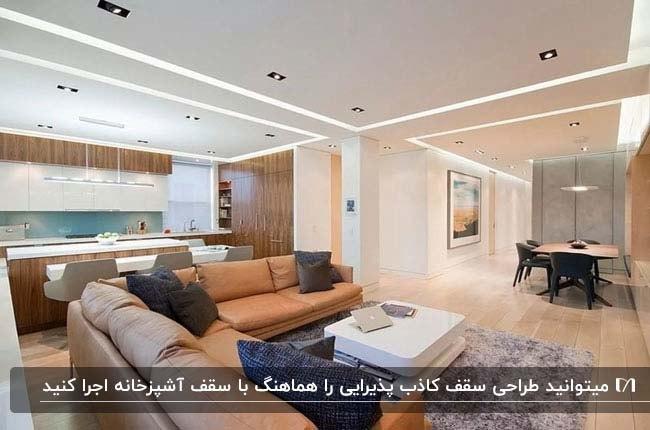 نشیمن و آشپزخانه ای در امتداد هم با سقف کاذب هماهنگ و مبلمان ال شکل چرم قهوه ای