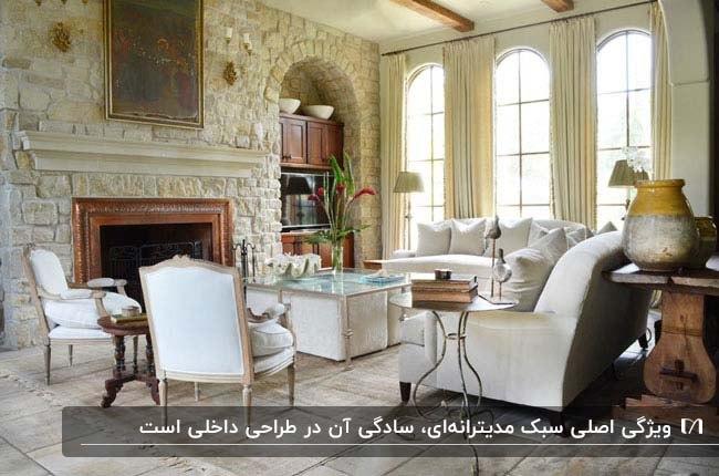 نشیمنی به سبک مدیترانه ای با مبلمان سفید و شومینه ای با فریم چوبی اما دیوار سنگی