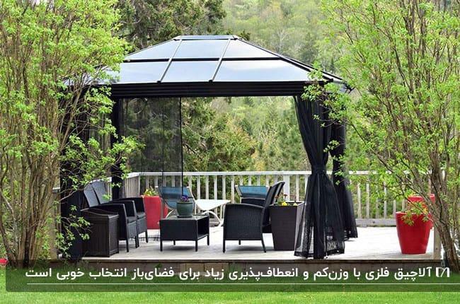 تصویری سایبان فلزی مشکی با میز و صندلی های حصیری مشکی در فضای سبز