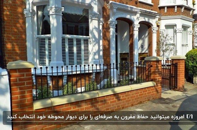 نرده های مشکی روی دیوار کوتاه بیرون خانه ای با نمای آجری قرمز