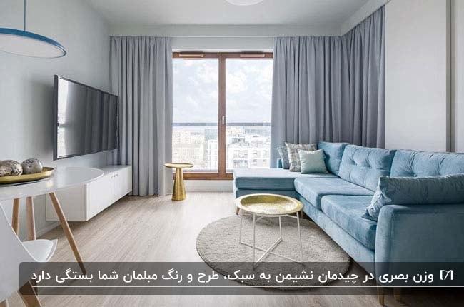 تصویر نشیمنی مربعی با یک کاناپه آبی و پرده های طوسی و تلویزیون روی دیوار