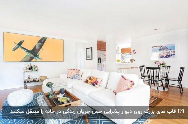یک نشیمن روشن با مبلمان سفید و تابلوهای بزرگ روی دیوار و کفپوش چوبی و فرش سبزآبی