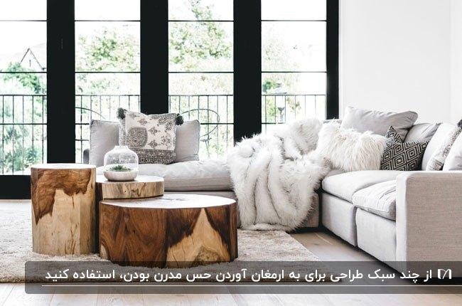 تصویر یک نشیمن مدرن با مبلمان ال کرم و میزهای گرد چوب طبیعی