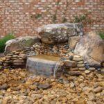 آبنمایی سنگی که با ترکیب تخته سنگ ها و قلوه سنگ ها در کنار گیاهان در حیاط ساخته شده است