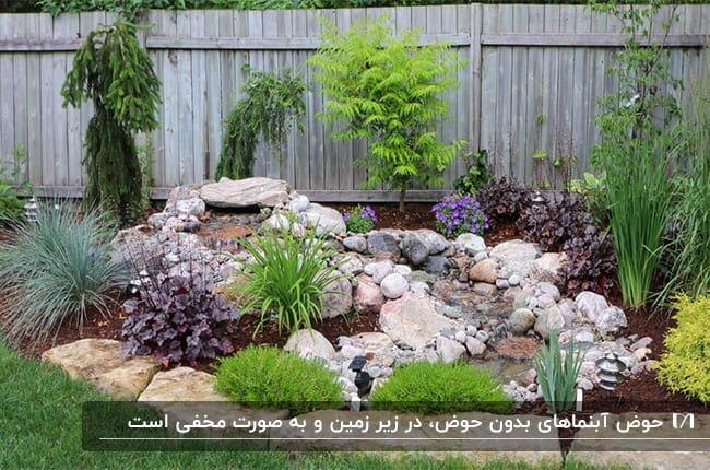 آبنمای حیاطی بدون حوض که با سنگ های ریز و درشت و گل ها و بوته های سبز ساخته شده