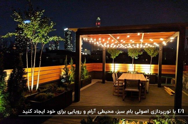 بام سبزی با پرگولای چوبی که سقفش با چراغ نورپردازی شده است و میز وصندلی هایی زیرش