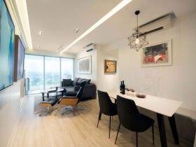 نشیمن مستطیل بلندی با مبلمان چرم مشکی به همراه یک میز سفید و صندلی های مشکی و سقف کاذب