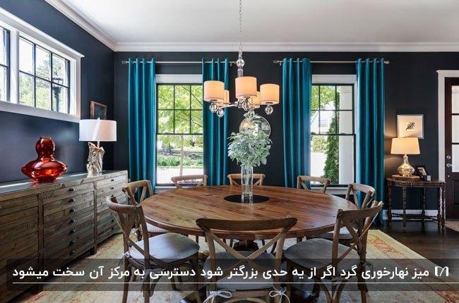 تصویری از یک سالن با پرده های آبی و میزنهارخوری گرد چوبی به همراه صندلی هایش