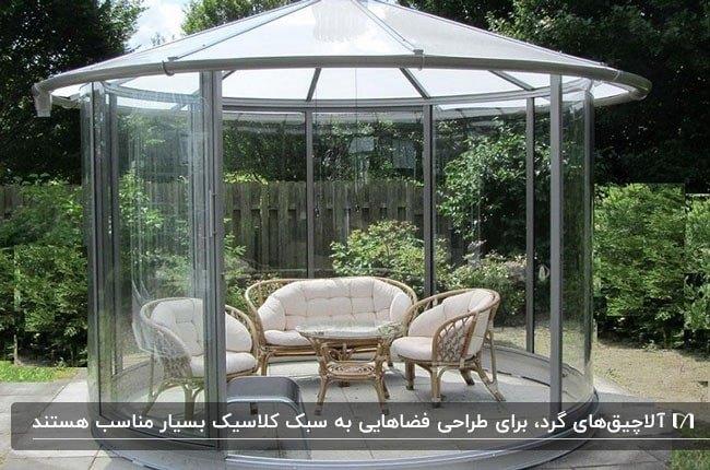 تصویر یک سایبان شیشه ای گرد با با فریم فلزی و سقف نیمه شفاف و مبلمان حصیری با پارچه شیری