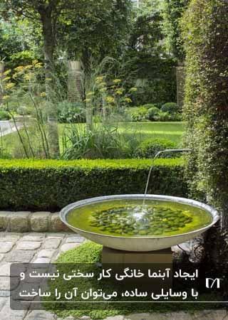 تصویر حوضچه آبنمایی با قلوه سنگ در یک باغ سبز