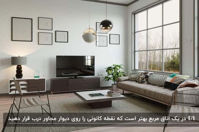 تصویر یک نشیمن مربع روشن با کاناپه کرم رنگ مجاور تلویزیون و میز جلو مبلی مربع