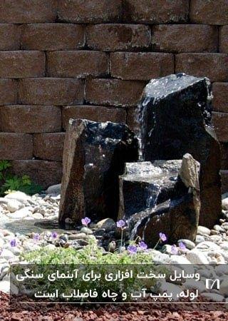 آبنمایی با سه تکه سنگ ایستاده روی زمین در باغ
