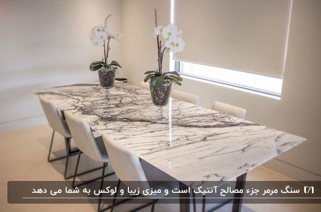 میز نهارخوری با رویه سنگی سفید و مشکی و صندلی های سفید