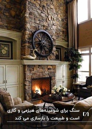 تصویر خانه ای به سبک روستاسس با شومینه سنگی مقابل مبلمان