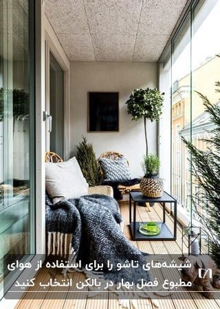 تراس بسته باریکی با صندلی و میز و گلدان های گل با شیشه های تاشو