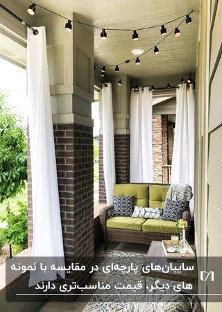 بالکن باریک و بلندی با ستون های نیمه آجری، مبل دو نفره قهوه ای و سبز و پرده های سفید دیوار