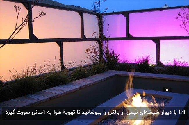 تراسی که با شیشه های مات صورت و بنفش پوشیده شده است به همراه گودال آتش