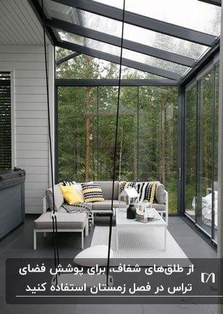 تراسی شیک با مبل ال شکل طوسی و سقف و دیواره های طلقی شفاف
