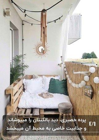 بالکنی با پالت چوبی و دشک سفید برای نشستن و حصیر برای دیوار آن