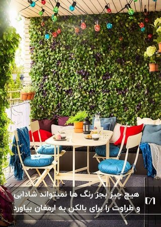 بالکنی با دیوار سبز و میز و صندلی های کرم با کوسن های رنگی