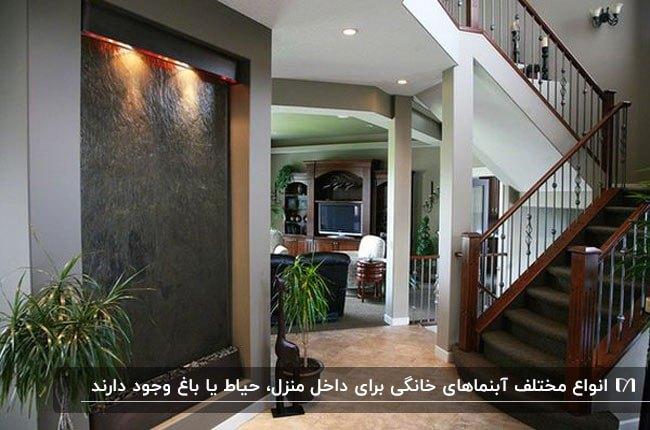 تصویر ورودی خانه ای با آبنمای دیواری رو بروی راه پله چوبی