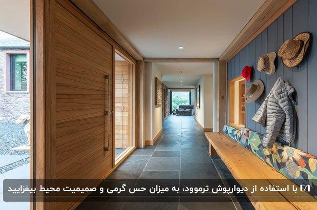 تصویر یک ورودی با درب چوبی و دیوارپوش ترموود رنگ شده و کفپوش خاکستری