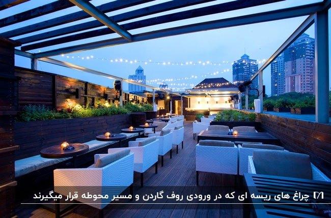 تصویر رستورانی در روف گردن که با چراغ های ریسه ای نورانی شده است