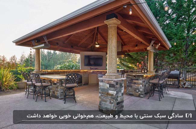 تصویر یک آلاچیق به سبک سنتی با ستون های سنگی و سقف شیب دار و صندلی های فلزی پشت کانتر