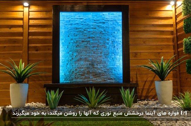 آبنمایی روی دیوار چوبی در حیاط با نورهای مخفی آبی و سنگ ریزه برای فضای پایین آبنما