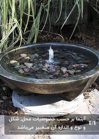 حوضچه آبنمایی که با قلوه سنگ های ریز و درشت پر شده است