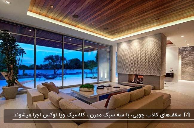 یک پذیرایی بزرگ با یک دیوار شیشه ای، مبلمان ال شکل کرم رنگ رو به روی شومینه و سقف کاذب چوبی