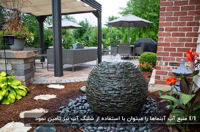 حیاط سرسبز ویلایی با دیوار آجری و آبنمای حیاطی سنگی گرد
