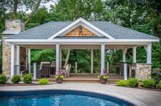 آلاچیقی با چهارچوب فلزی و سقف طوسی شیروانی در کنار استخر