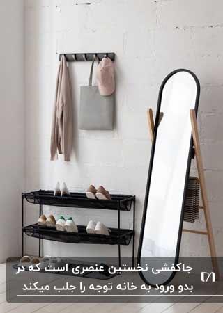 جاکفشی پارچه مشکی در ورودی بایک آینه بیضی و فریم مشکی و آویز دیواری برای لباس