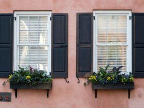 تصویری از دو پنجره سفید با حفاظ و فلاورباکس های قهوه ای تیره بر روی دیوار صورتی کمرنگ
