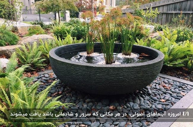 آبنمایی مانند یک کاسه گود وسط باغچه با سه گلدان گل درونش
