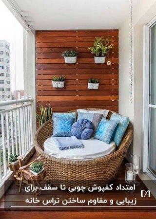 تراسی با کفپوش و دیوارپوش چوبی و مبل راحتی دایره ای و کوسن های آبی
