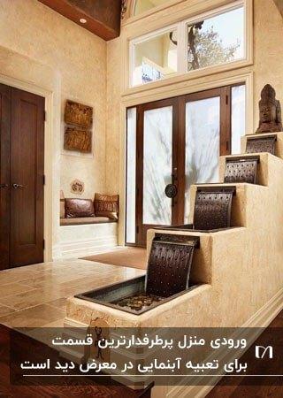 ورودی کرم و قهوه ای خانه ای با آبشار پلکانی و یک مجسمه بالای آبنما