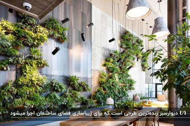 تصویری از یک نشیمن با یک دیوار سبز و چراغ های آویز با میز و صندلی های چوبی