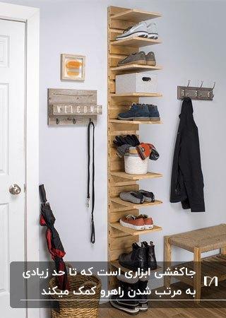 تصویر یک جاکفشی چوبی استاده چند طبقه با چوب لباسی روی دیوار و یک نیمکت چوبی کنارش