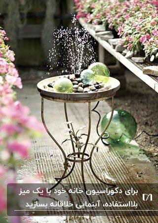 تصویر آبنمایی که با یک میز قدیمی، تعدادی قلوه سنگ و گل های اطرافش ساخته شده است