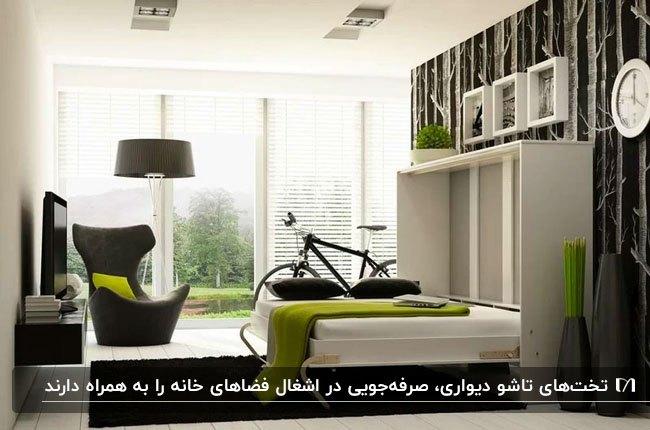 اتاق خوابی با کمد سفید، تخت تاشوی دیوار سفید با روتختی سبز و بالشت مشکی و یک صندلی سبز کنار تخت