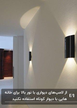 راهرویی با دیوارهای سفید و چراغ های دیواری مشکی با نور دو طرفه بالا و پایین