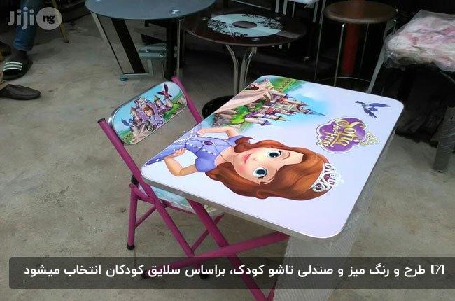 تصویری از یک میز و صندلی تاشوی صورتی کودک با طرح های کارتونی کودکانه