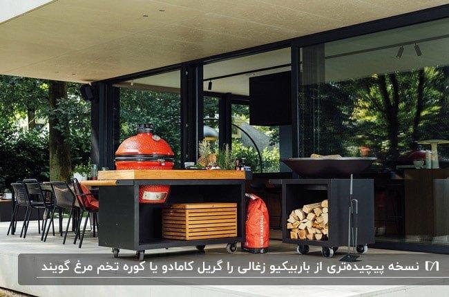 تصویر کباب پز کامادو قرمز رنگ با میز کاری چوبی و مشکی و مقداری هیزم در میز