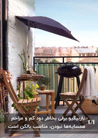 بالکن کوچک و باریکی با میز و صندلی های چوبی و کباب پز کوچک ایستاده کنار سایبان دیواری