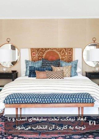 اتاق خوابی با تخت دو نفره سفید، کوسن های آبی و کرم، دو آینه گرد دو طرف تخت و پاف نیمکت